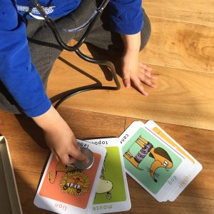 Young boy with a stethoscope pretending to listen to a lion on a flashcard