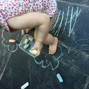 child drawing outside with floor chalks